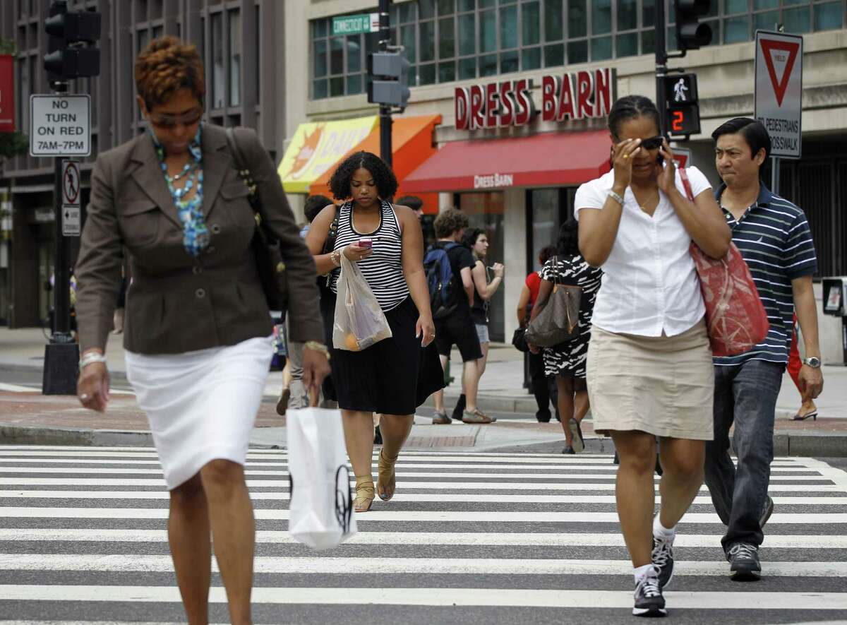In this July 10, 2012 photo, pedestrians cross K Street and Connecticut Ave. NW near the Farragut North Metro Entrance in downtown Washington. Across the country on city streets, in suburban parking lots and in shopping centers, there is usually someone strolling while talking on a phone, texting with their head down, listening to music, or playing a video game. The problem isn't as widely discussed as distracted driving, but the danger is real. (AP Photo/Pablo Martinez Monsivais)