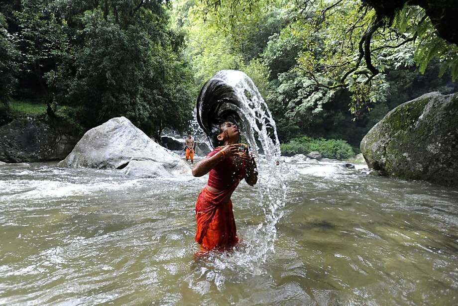 A Hindu devotee takes a bath in the Bagmati River for Shravan festivities before heading towards the Pashupatinath Temple to offer prayers to Lord Shiva, Hindu god of destruction, in Sundarijal on the outskirts of Kathmandu on July 30, 2012. According to the Nepali calendar, Shravan is considered the holiest month of the year with each Monday of the month - known as Shravan Somvar - is when worshippers offer prayers for a happy and prosperous life. Photo: Prakash Mathema, AFP/Getty Images