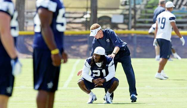 Dallas Cowboys head coach Jason Garrett pauses with player Dallas Cowboys cornerback Mike Jenkins during the first day of their 2012 training camp Monday July 30, 2012 in Oxnard, CA. Photo: Edward A. Ornelas, San Antonio Express-News / © 2012 San Antonio Express-News