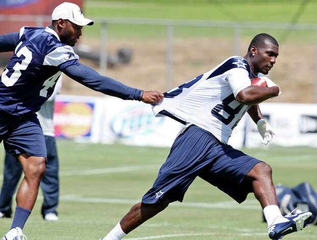 Dallas Cowboys wide receiver Dez Bryant (right) looks for room around Dallas Cowboys safety Gerald Sensabaugh at practice during the first day of their 2012 training camp Monday July 30, 2012 in Oxnard, CA. Photo: Edward A. Ornelas, San Antonio Express-News / © 2012 San Antonio Express-News