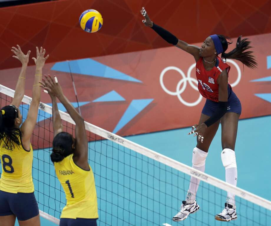 United States' Destinee Hooker, right, spikes the ball over Brazil's Jaqueline Carvalho (8) and Fabiana Claudino (1) during a women's preliminary volleyball match at the 2012 Summer Olympics, Monday, July 30, 2012, in London. (Jeff Roberson / Associated Press)