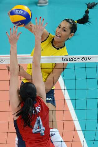 Brazil's Jaqueline Carvalho (top) spikes as US's Lindsey Berg attempts to block during the women's preliminary pool B volleyball match between USA and Brazil of the 2012 London Olympic Games in London on July 30, 2012. (KIRILL KUDRYAVTSEV / AFP/Getty Images)
