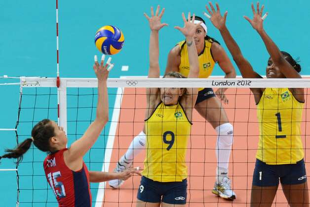 US's Logan Tom (L) spikes as Brazil's Fernanda Ferreira (C) and Fabiana Claudino (R) attempt to block during the women's preliminary pool B volleyball match between USA and Brazil of the 2012 London Olympic Games in London on July 30, 2012. (KIRILL KUDRYAVTSEV / AFP/Getty Images)