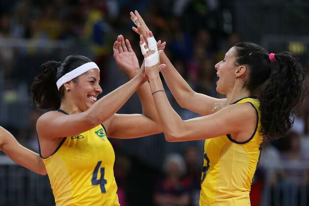 Paula Pequeno of Brazil and team mate Sheilla Castro of Brazil celebrate winning a point in the Women's Volleyball Preliminary match between the United States and Brazil on Day 3 of the London 2012 Olympic Games at Earls Court on July 30, 2012 in London, England. (Elsa / Getty Images)