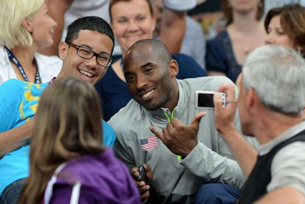 US basketball player Kobe Bryant (C) poses for a photograph as he attends the women's preliminary pool B volleyball match between the US and Brazil in the 2012 London Olympic Games in London on July 30, 2012. (KIRILL KUDRYAVTSEV / AFP/Getty Images)