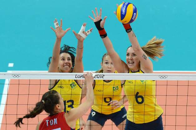US Logan Tom (L, down) spikes as Brazil's Sheilla Castro (2L) and Thaisa Menezes (R) attempt to block, as Brazlian Fernando Ferreira (2ndR) looks on, during the women's preliminary pool B volleyball match between USA and Brazil in the 2012 London Olympic Games in London on July 30, 2012. (KIRILL KUDRYAVTSEV / AFP/Getty Images)