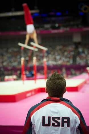 Jonathan Horton watches as Danell Leyva performs on the parallel bars during the men's gymnastics team final at the 2012 London Olympics on Monday, July 30, 2012. The USA finished in 5th place. (Smiley N. Pool / Houston Chronicle)
