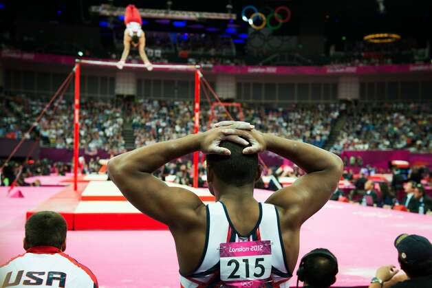 John Orozco of the USA watches as Danell Leyva performs on the horizontal bar during the men's gymnastics team final at the 2012 London Olympics on Monday, July 30, 2012. The USA finished in 5th place. (Smiley N. Pool / Houston Chronicle)