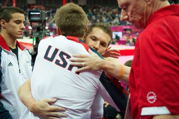 Jonathan Horton, facing, gets a hug from Sam Mikulak as Jake Dalton, left, and coach Kevin Mazeika, right, look on following the men's gymnastics team final at the 2012 London Olympics on Monday, July 30, 2012. The USA finished in 5th place. (Smiley N. Pool / Houston Chronicle)