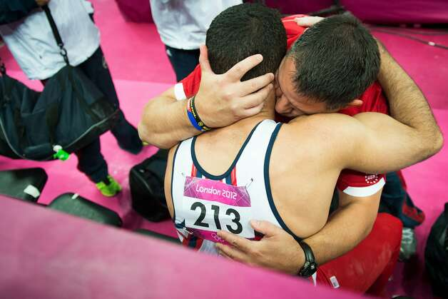 Danell Leyva is consoled by USA assistant coach Tom Meadows following the men's gymnastics team final at the 2012 London Olympics on Monday, July 30, 2012. The USA finished in 5th place. (Smiley N. Pool / Houston Chronicle)