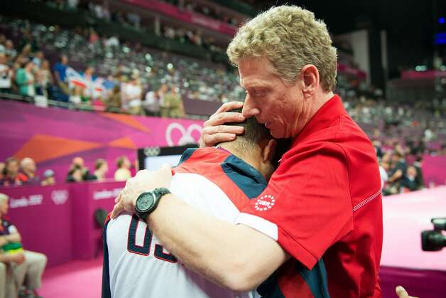 Coach Kevin Mazeika of Houston consoles Danell Leyva following the men's gymnastics team final at the 2012 London Olympics on Monday, July 30, 2012. The USA finished in 5th place. (Smiley N. Pool / Houston Chronicle)