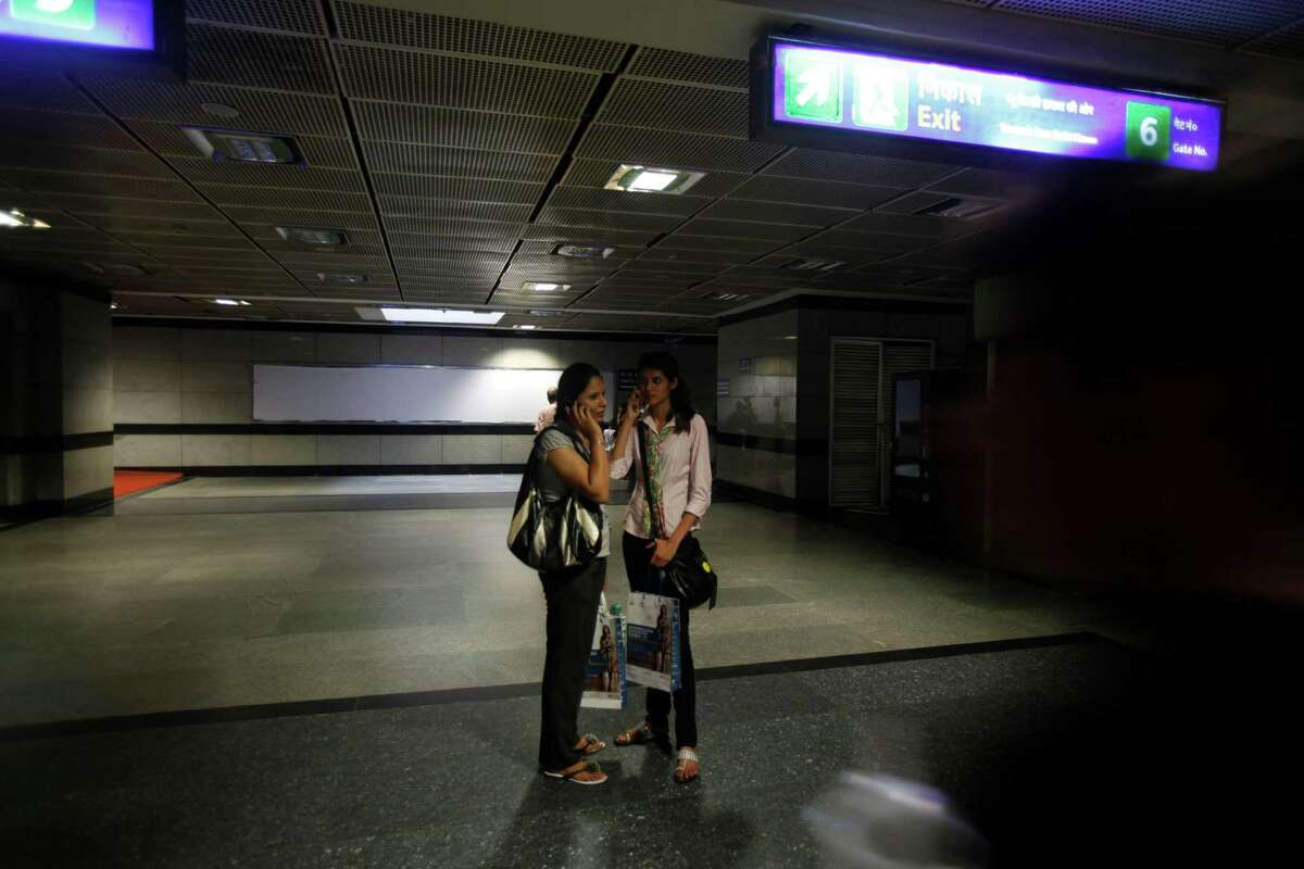 Commuters talk on mobile phone inside a Metro station after Delhi Metro rail services were disrupted following power outage in New Delhi, India, Tuesday, July 31, 2012. A massive blackout hit northern and eastern India on Tuesday afternoon, leaving 600 million people without electricity in one of the world's most widespread power failures. The outage came just a day after India's northern power grid collapsed for several hours leaving cities and villages across eight states powerless.(AP Photo/ Rajesh Kumar Singh)