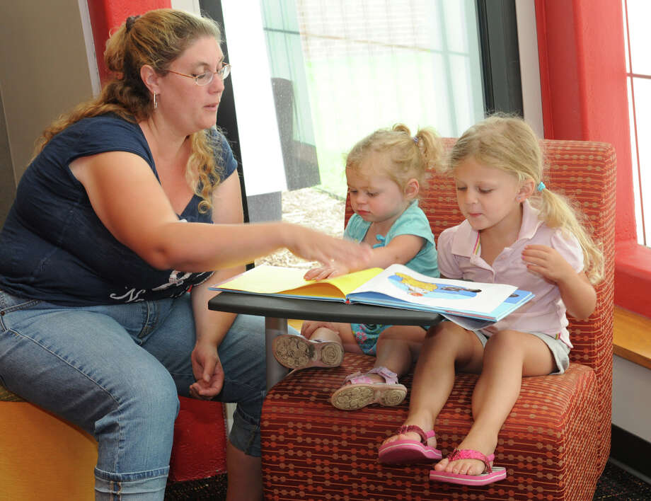 Shannon Loveland of Scotia reads with her daughters Becky and Catie in the Schenectady Foundation Early Learning Corner at the Schenectady County Public Library during the official opening of the $3 million, 6,700 square foot expansion of the central downtown branch on Monday, July 30, 2012 in Schenectady, N.Y. The expansion includes the Wright family Children's Center with conference rooms upstairs. (Lori Van Buren / Times Union) Photo: Lori Van Buren