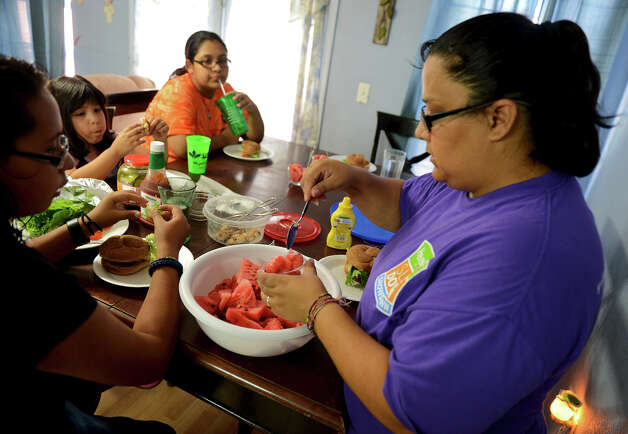 Dina Lopez (right) loads a small cup with watermelon as her daughters enjoy chicken burgers for dinner in their west side home.  Lopez is participating in the HEB Slim Down Showdown with the help of her family.  John Albright / Special to the Express-News. Photo: JOHN ALBRIGHT, Special To The Express-News