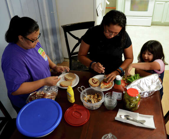 Dina Lopez (left) gets some help from her daughters Maria Inez Perez (center) and Liliana Lopez (right) as they make chicken burgers for dinner in their west side home.  Lopez is participating in the HEB Slim Down Showdown with the help of her family.  John Albright / Special to the Express-News. Photo: JOHN ALBRIGHT, Special To The Express-News