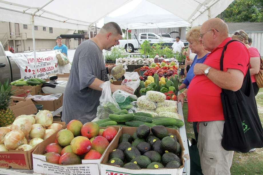 Sam Cribbs helps customers Jim Hagg and Lucy Parsley of Kemah bag fresh vegetables from Froberg's Farm in Alvin at the Clear Lake Shores Farmers' Market. Photo: Pin Lim / Copyright Pin Lim.