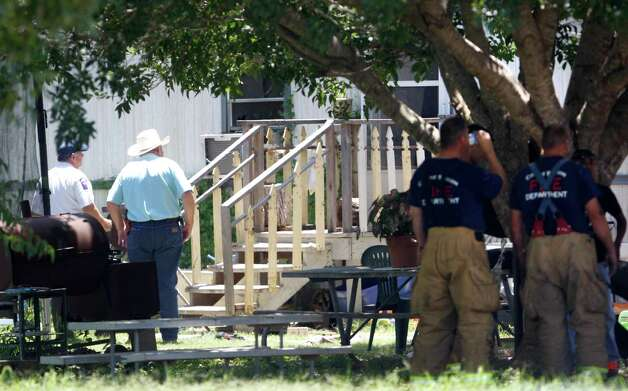 Officials stand Tuesday July 31, 2012 near the scene of a fatal fire in on Los Nietos Lane in Guadalupe County near Seguin. Two children -- age 5 and 15 -- and their mother died in the fire. A fourth person survived. Photo: William Luther, San Antonio Express-News / © 2012 San Antonio Express-News