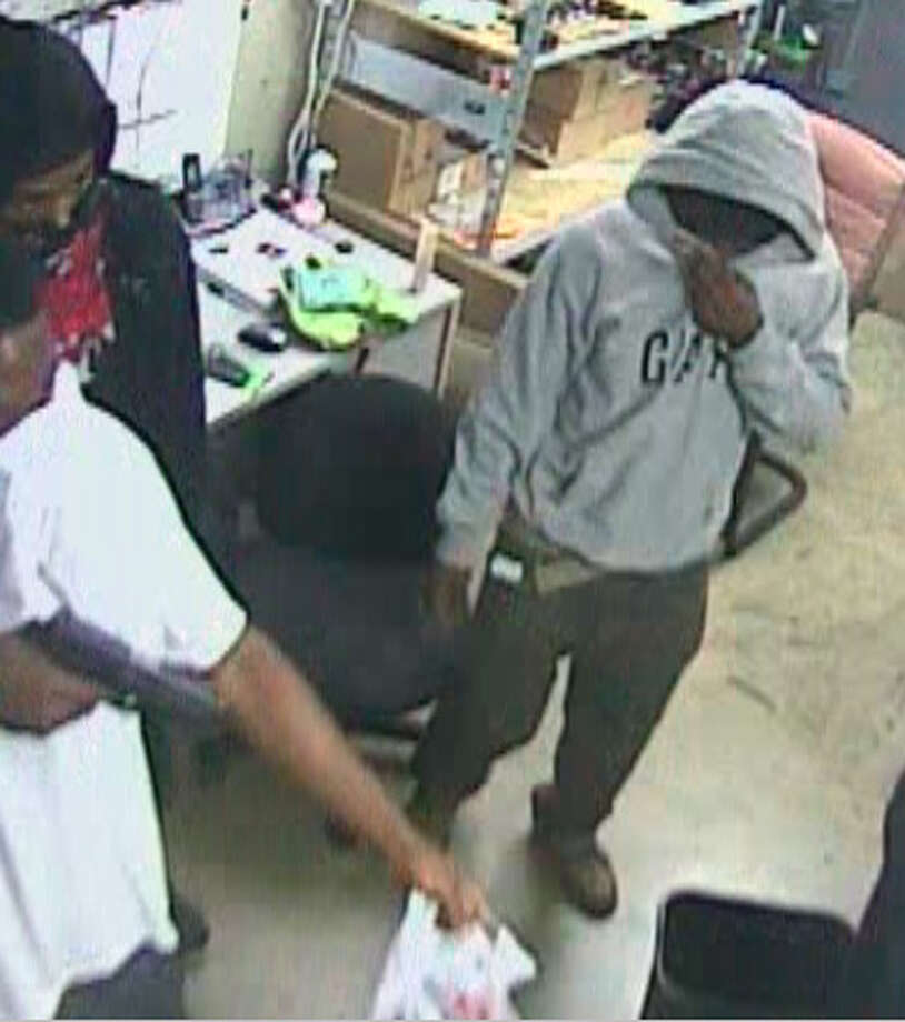 Surveillance photos show three men taking over a West U. electronics store Sunday. (Crime Stoppers photo) Photo: Handout