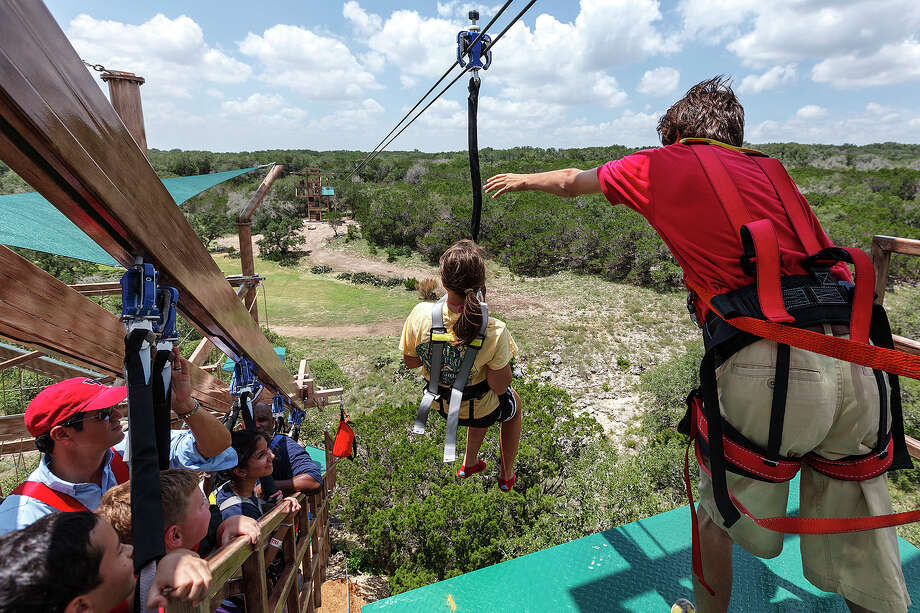 Kevin Johnson (right) sends Emily Lucas on her way to one of the two outlying towers on a zip line at the new Canopy Challenge Adventure Course and Zip Lines at Natural Bridge Caverns on July 26, 2012.  The 60-foot structure is the largest of its kind in the world and features four levels of challenging obstacle courses and four zip lines.  Photo by Marvin Pfeiffer / Prime Time Newspapers Photo: MARVIN PFEIFFER, Marvin Pfeiffer / Prime Time Newspapers / Prime Time Newspapers 2012