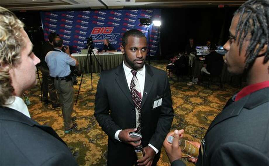 Cincinnati linebacker Maalik Bomar, center talks with offensive tackle Austen Bujnoch, left, and defensive end Walter Stewart, right, during the Big East Conference NCAA college football media day, Tuesday, July 31, 2012, Newport, R.I. (AP Photo/Stew Milne)