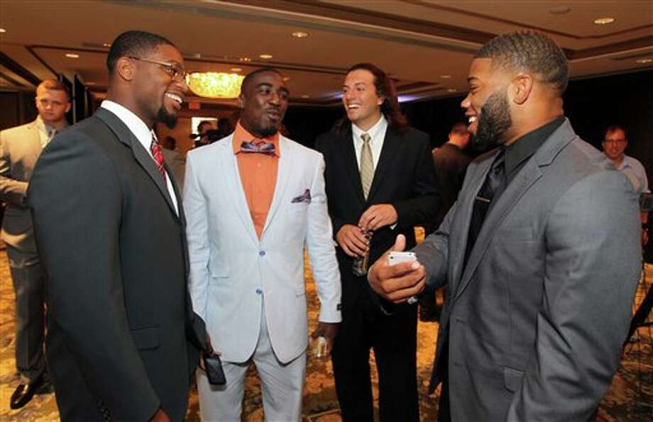 University of South Florida football players from left, Sam Barrington, Kayvon Webster, Evan Landi and B.J. Daniels wait to be interviewed during the Big East Conference NCAA college football media day, Tuesday, July 31, 2012, Newport, R.I. (AP Photo/Stew Milne)