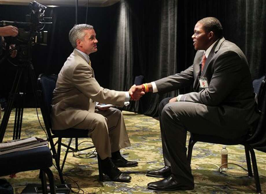 Syracuse defensive tackle Jay Bromley, right, shakes hands with YNN Syracuse sports director Mark Larson following an interview at the Big East Conference NCAA college football media day, Tuesday, July 31, 2012, Newport, R.I. (AP Photo/Stew Milne)