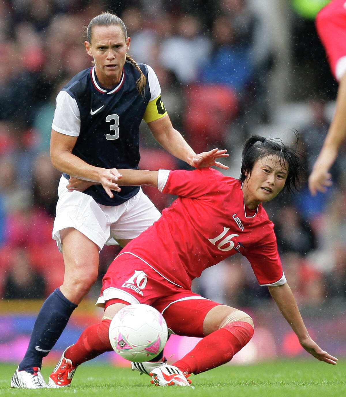 North Korea's Kim Song Hui, center, fights for the ball against the United States' Christie Rampone during their group G women's soccer match at the London 2012 Summer Olympics, Tuesday, July 31, 2012, at Old Trafford Stadium in Manchester, England.