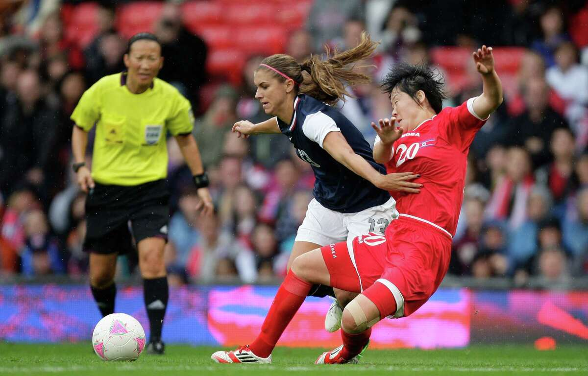 United States' Alex Morgan, center, keeps the ball from North Korea's Choe Yong Sim during their group G women's soccer match at the London 2012 Summer Olympics, Tuesday, July 31, 2012 at Old Trafford Stadium in Manchester, England.