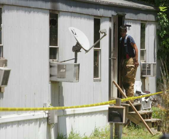 A fire fighter examines the scene Tuesday July 31, 2012 of a fatal fire on Los Nietos Lane in Guadalupe County near Seguin. Two children -- age 5 and 15 -- and their mother died in the fire. A fourth person survived. Photo: William Luther, San Antonio Express-News / © 2012 San Antonio Express-News