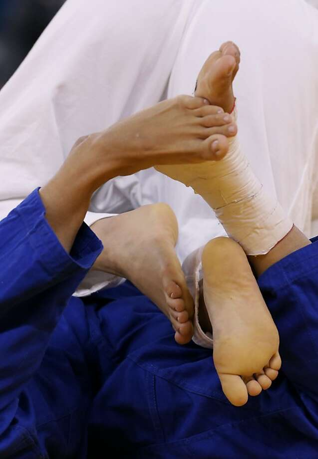 Feet get tangled during a match between Yoshie Ueno of Japan and Marijana Miskovic of Croatia in the women's 63-kg judo competition at the 2012 Summer Olympics, Tuesday, July 31, 2012, in London. (AP Photo/Paul Sancya) Photo: Paul Sancya, Associated Press