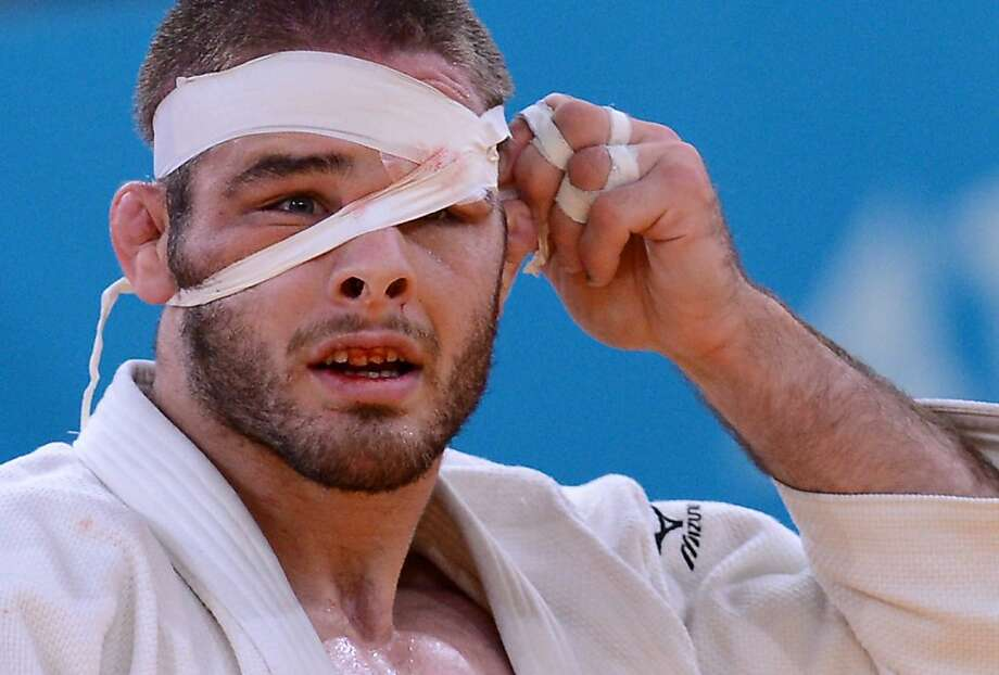 TOPSHOTS  United States' Travis Stevens adjusts his bandage as he competes with Germany's Ole Bischof (blue) during their men's -81kg judo contest semi-final match of the London 2012 Olympic Games on July 31, 2012 at the ExCel arena in London. AFP PHOTO / FRANCK FIFEFRANCK FIFE/AFP/GettyImages Photo: Franck Fife, AFP/Getty Images