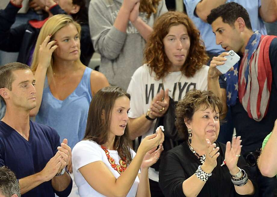 Debbie Phelps (R) and Hiraly (C) mother and sister of US swimmer Micheal Phelps, applaud next to Israel's model Bar Refaeli (2L,up) and US surfeur Shaun White (C,up) during the podium ceremony of the men's 4x200m freestyle relay final during the swimming event at the London 2012 Olympic Games on July 31, 2012 in London. AFP PHOTO / CHRISTOPHE SIMONCHRISTOPHE SIMON/AFP/GettyImages Photo: Christophe Simon, AFP/Getty Images