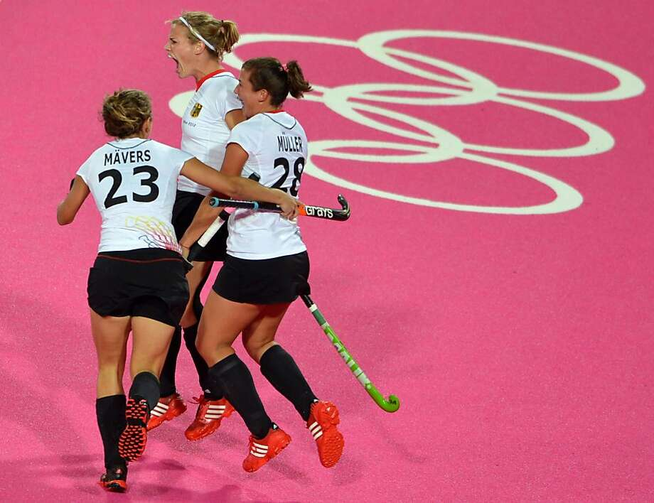 Teammates Marie Mavers (L) and Julia Mueller celebrate with Katharina Otte of Germany after scoring a goal against Australia during their London 2012 Olympic Games preliminary round women's field hockey match at the Riverbank Arena in London on July 31, 2012.  AFP PHOTO/ INDRANIL MUKHERJEEINDRANIL MUKHERJEE/AFP/GettyImages Photo: Indranil Mukherjee, AFP/Getty Images