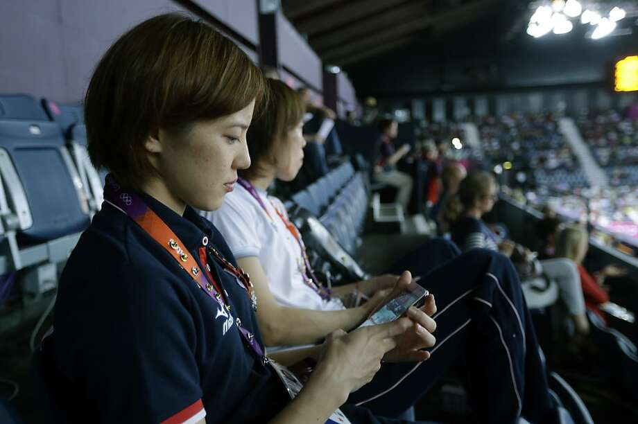 Japan's Miyuki Maeda looks at her iphone as she watches badminton matches in progress with a phone in her hand at the 2012 Summer Olympics, Tuesday, July 31, 2012, in London. The immediacy and public nature of Twitter and its propensity to induce off-the-cuff irreverence, and sometimes breathtaking ugliness, has added a new and chaotic element to the Olympics, where everything from urine samples to sponsors' logos to London traffic is arranged with attention to detail worthy of a royal wedding.(AP Photo/Saurabh Das) Photo: Saurabh Das, Associated Press