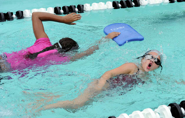Searra Diggs, 11, of Danbury, left, and Arianna Petta, 7, of Brookfield, swim freestyle during the Western Connecticut YMCA Makos Swim Clinic, Tuesday, July 31, 2012. Photo: Carol Kaliff / The News-Times