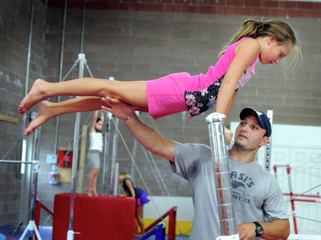 Sarah Hensel, 9, of Monroe, is coached on the uneven bars by Vasi Cioana, owner of Vasi's Gymnastics in Newtown, Tuesday, July 31, 2012. Photo: Carol Kaliff / The News-Times