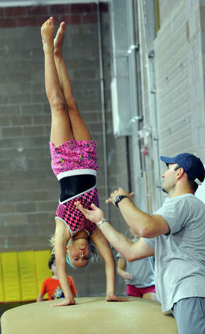 katie Garner, 9, of Newtown, does a handspring on the vault, coached by Vasi Cioana, owner of Vasi's Gymnastics in Newtown, Tuesday, July 31, 2012. Photo: Carol Kaliff / The News-Times