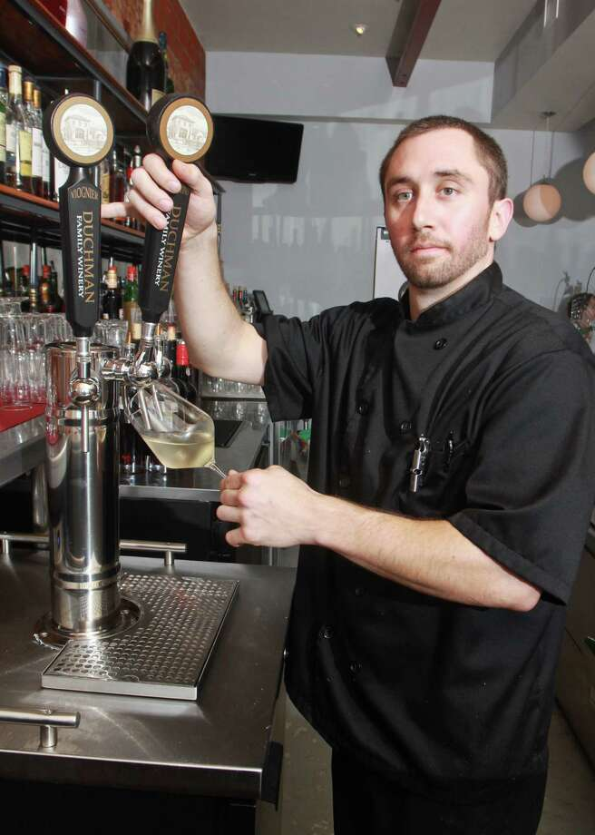 (For the ChronicleGary Fountain, July 24, 2012)  Stefan Breitweiser using a tap for a glass of Duchman Bermantino wine at L'Olivier Restaurant & Bar. Photo: Gary Fountain / Copyright 2012 Gary Fountain.