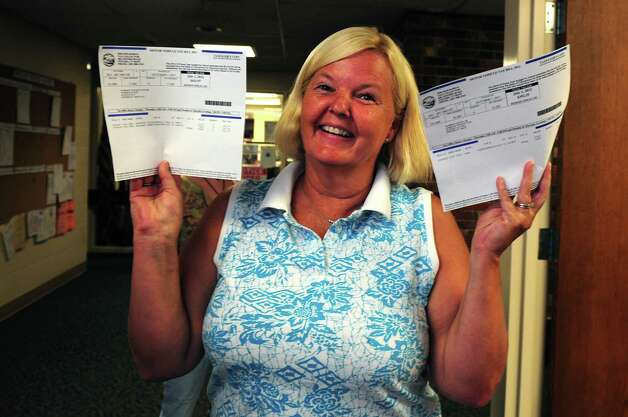 Town resident Kathy Harrick holds up her receipts after paying taxes to the Oxford tax collector Tuesday, July, 31, 2012.  Harrick was falsely placed on the tax delinquent list under the management of former tax collector Karen Guillet, who pleaded guilty Tuesday to first-degree larceny.  Harrick had to provide the town with several years worth of records to clear her name. Photo: Autumn Driscoll / Connecticut Post