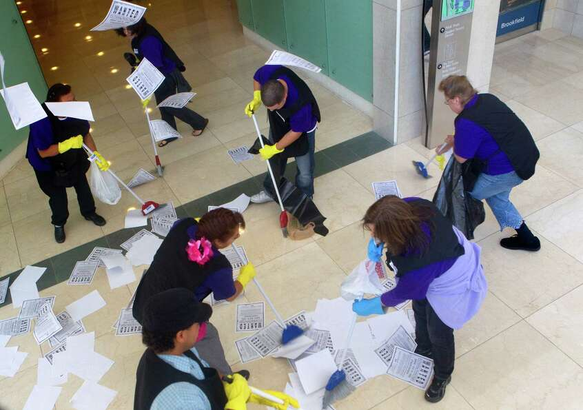 Protestors mockingly sweep up papers as part of their protest of janitors' current wages at One Alle