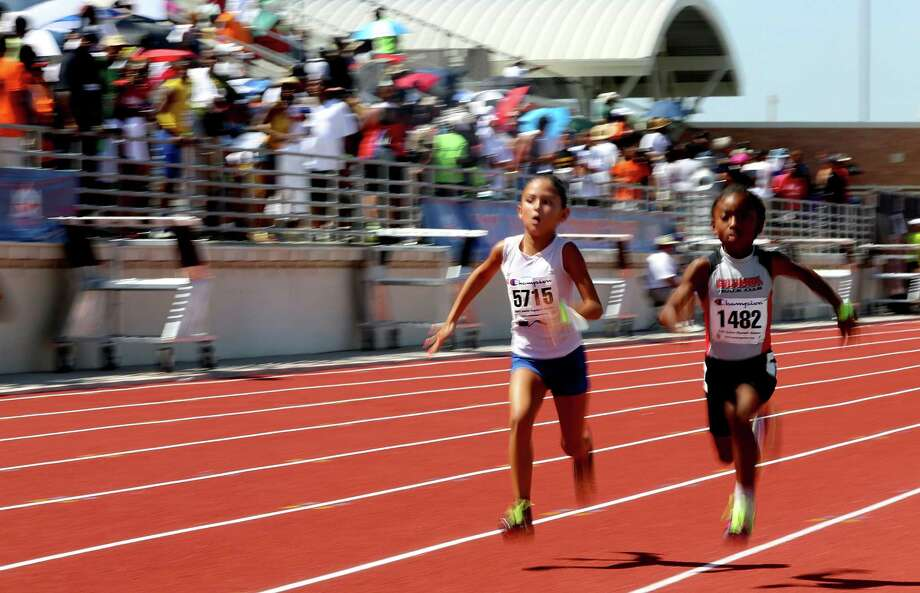 Lexi Martin, left, races against Brianna Hinds, 8, from San Antonio in the 100-meter dash at the AAU Junior Olympics in Humble. The annual competition brings together young athletes from across the country. Photo: Thomas B. Shea / © 2012 Thomas B. Shea