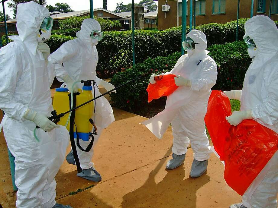 "A picture taken on July 28, 2012 shows officials from the World Health Organization wearing protective gear as they prepare to enter Kagadi Hospital in Uganda's western Kibale district, around 200 kilometres (125 miles) from Kampala. World Health Organisation (WHO) spokesman Tarik Jasarevic confirmed the first death from the deadly Ebola virus in the capital Kampala, but noted that ""so far no infections have occurred"" there. Seven people suspected of having the virus have been isolated in Kigadi hospital, Health Minister Christine Ondoa said.  AFP PHOTO / ISAAC KASAMANIISAAC KASAMANI/AFP/GettyImages Photo: Isaac Kasamani, AFP/Getty Images"