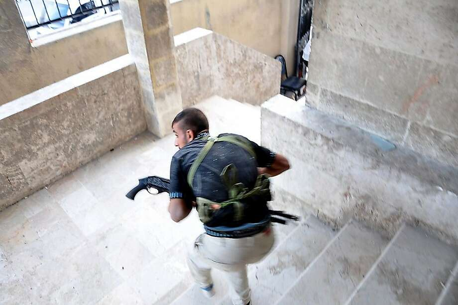 A Syrian rebel takes position during clashes with government troops at a police station in the Salhin district of the northern city of Aleppo on July 31, 2012. Syrian rebels attacked key military targets and overran two police stations in Aleppo, killing 40 officers, a watchdog said, as the pivotal battle for the commercial capital raged.      TOPSHOTS/AFP PHOTO/PIERRE TORRESPierre Torres/AFP/GettyImages Photo: Pierre Torres, AFP/Getty Images