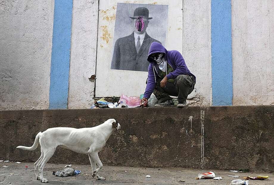 """In this July 29, 2012 photo, a masked artist who calls himself the Urban Maeztro and prefers to remain anonymous for security reasons, stops to play with a street dog after pasting one of his """"interventions"""" on a street wall showing Rene Magritte's """"Son of Man,"""" substituting the apple covering the face of the suited subject in bowler hat with a pink grenade, in Tegucigalpa, Honduras. The 26-year-old graphic artist left his day job at an advertising agency to work on pieces like this one, to encourage Hondurans think about how violent their country has become.  (AP Photo/Fernando Antonio) Photo: Fernando Antonio, Associated Press"""