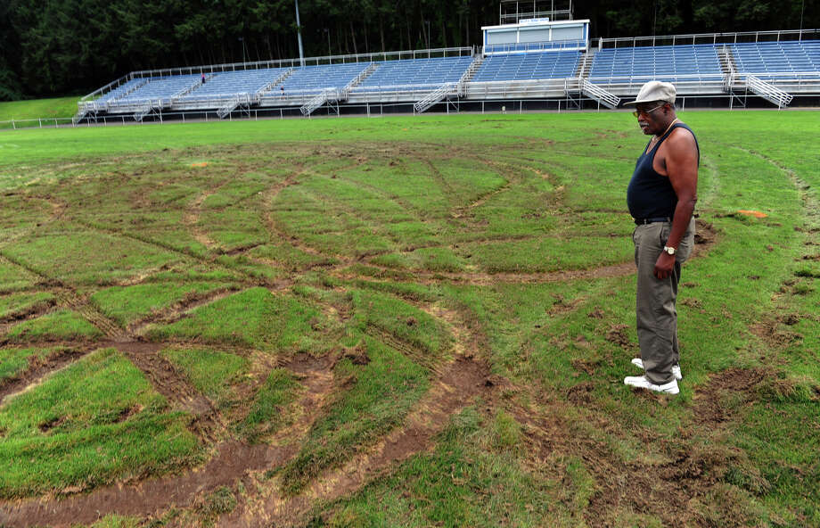 James Mills, a caretaker of the facilities at Nolan Field, surveys damage to the football field suspected to have been done with an ATV, in Ansonia, Conn. on Tuesday July 31, 2012. Photo: Christian Abraham / Connecticut Post