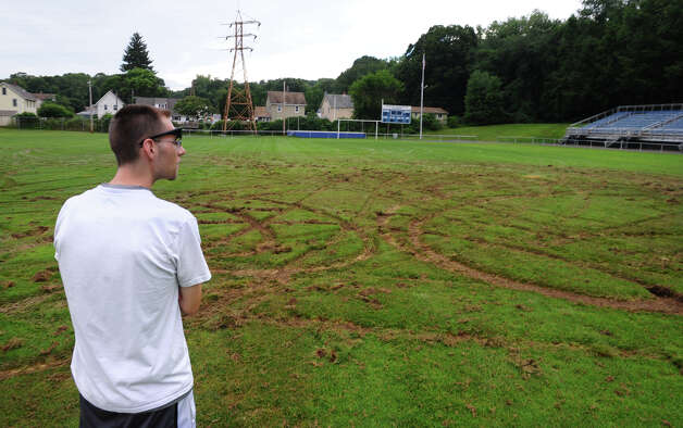 Resident James Pandolfi looks over severe damage done to the football field by a suspected ATV in the Nolan Field complex in Ansonia, Conn. on Tuesday July 31, 2012. Photo: Christian Abraham / Connecticut Post
