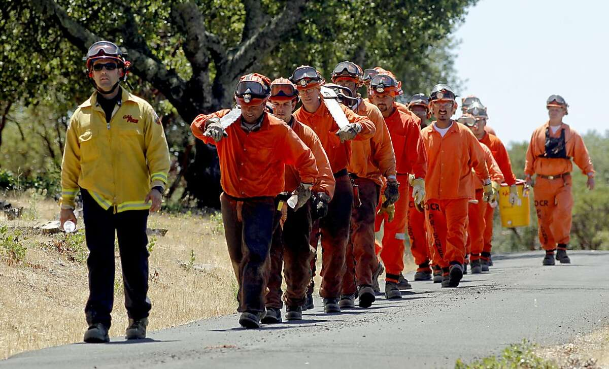Cal Fire Captain John Greenberg, leads Delta Crew 5, a Cal Fire inmate hand crew, on to their next assignment, as they work on a fuel reduction project in Solano County, Calif., on Tuesday July 31, 2012. Conservation Corps programs with the state of California prisons do a lot of the grunt work in fighting fires in the state. There are about 4,000 prisoners in the program right now, but these are low level offenders and in the future will be shifted to county jails instead of state prisons. That raises the possibility of losing thousands of these kinds of workers and that could cost the state a great deal of money to replace them.