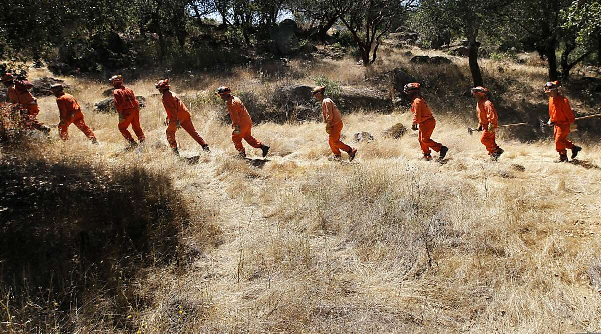 Delta Crew 5, a Cal Fire inmate hand crew from Suisun City, Calif., takes a break for lunch, as they work on a fuel reduction project in Solano County, Calif., on Tuesday July 31, 2012. Conservation Corps programs with the state of California prisons do a lot of the grunt work in fighting fires in the state. There are about 4,000 prisoners in the program right now, but these are low level offenders and in the future will be shifted to county jails instead of state prisons. That raises the possibility of losing thousands of these kinds of workers and that could cost the state a great deal of money to replace them.
