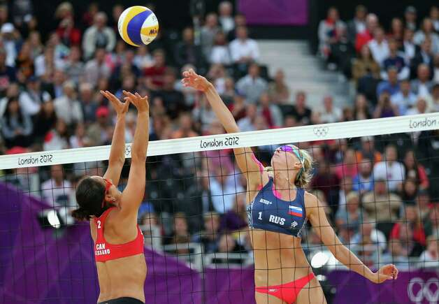 LONDON, ENGLAND - JULY 31:  Marie-Andree Lessard of Canada defends as Ekaterina Khomyakova of Russia pushes the ball over the net during the Women's Beach Volleyball Preliminary match between Canada and Russia on Day 4 at Horse Guards Parade on July 31, 2012 in London, England.  (Photo by Ryan Pierse/Getty Images) Photo: Ryan Pierse, Getty Images / 2012 Getty Images