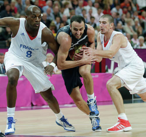 Argentina's Manu Ginobili (center) threads between France's Ali Traore (left) and fellow Spurs player Nando De Colo. Photo: Charles Krupa, Associated Press / AP